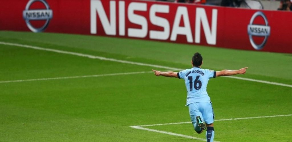 Agüero running towards supporters with a Nissan led in background.